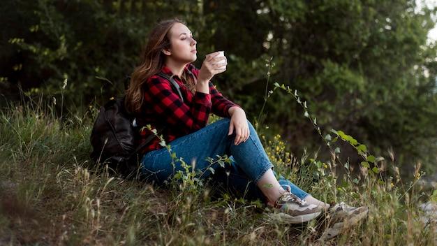 Donna piena del colpo che si siede sulla terra nella foresta