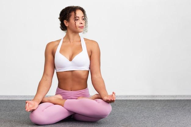 瞑想の位置に座っているフルショットの女性