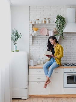 Full shot woman sitting on the kitchen countertop