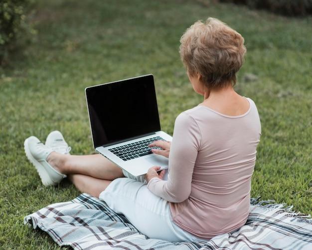 Donna piena del colpo che si siede sul computer portatile