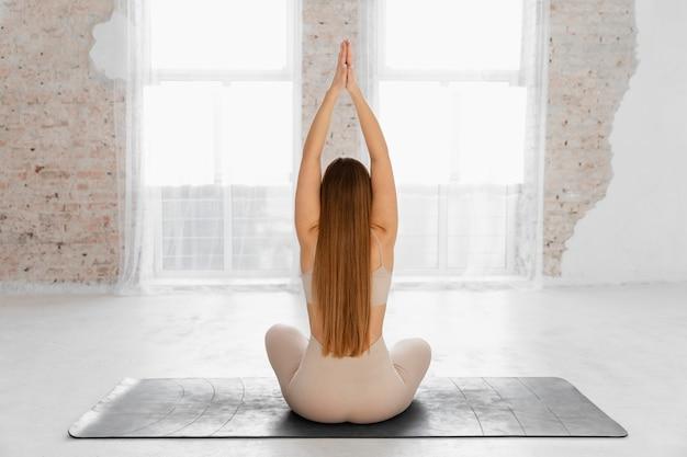 Full shot woman sitting on mat