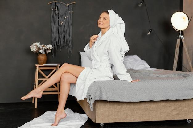 ベッドに座っているフルショットの女性