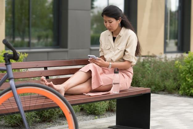 電話でベンチに座っているフルショットの女性