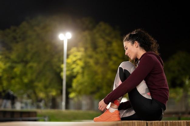 ベンチに座っているフルショットの女性