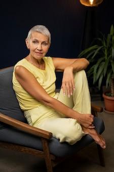 Полный снимок женщина, сидящая на стуле