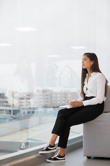 椅子に座っているフルショットの女性
