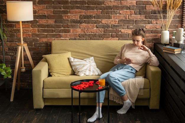ソファに座っているフルショットの女性