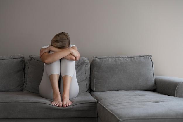 Полный выстрел женщина, сидящая на диване