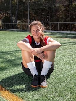 Полный выстрел женщина, сидящая на футбольном поле