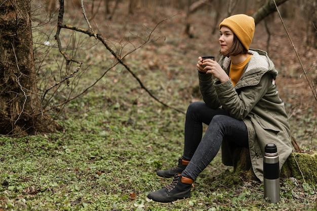 Полный выстрел женщина, сидящая на траве