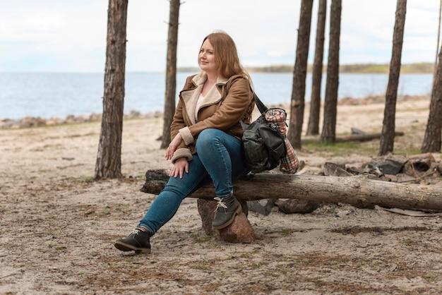 丸太に座っているフルショットの女性