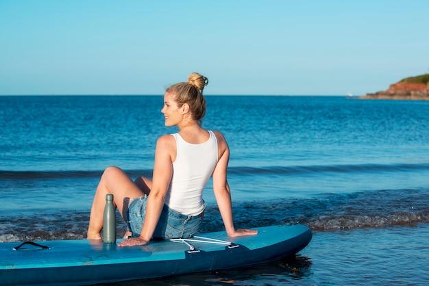 パドルボードに座っているフルショットの女性