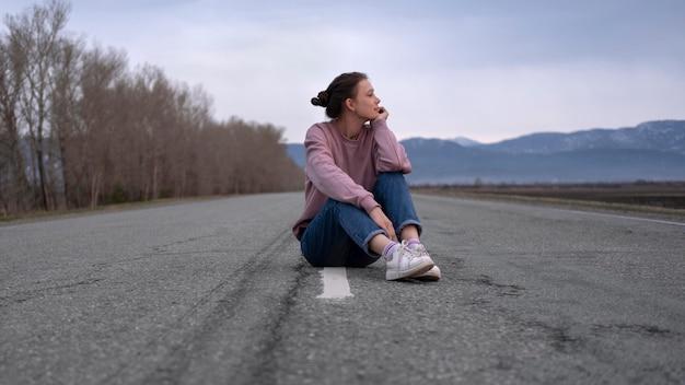 道路に座っているフルショットの女性