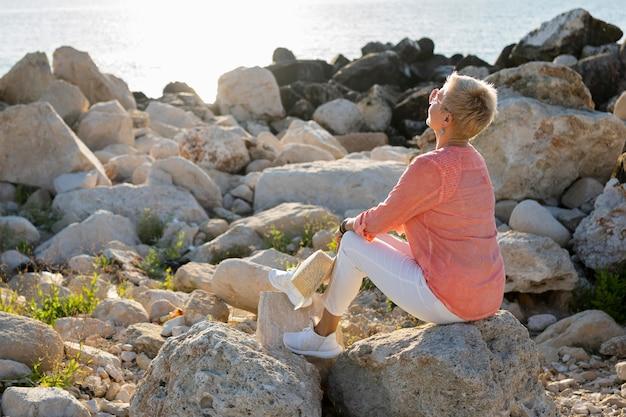 Полный выстрел женщина, сидящая на скале
