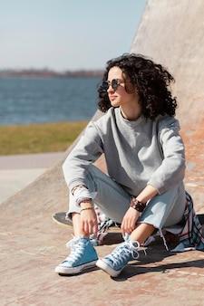 スケートボードに座っているフルショットの女性