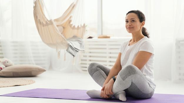 Полный снимок женщины, сидящей на коврике для йоги