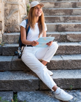 Donna piena del colpo che si siede sulle scale esterne con la mappa