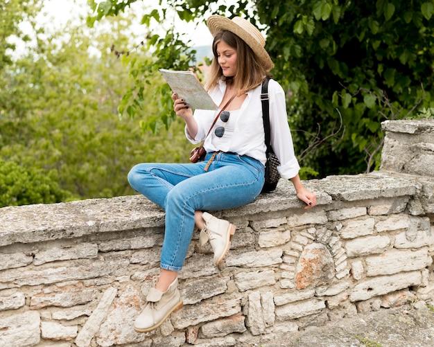 Full shot woman sitting outdoors