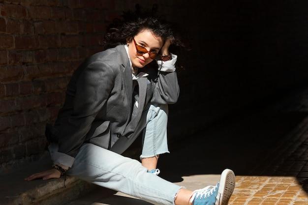 屋外に座っているフルショットの女性