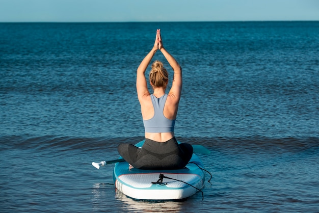 Full shot woman sitting on paddleboard