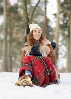 Donna piena del colpo che si siede sulla neve