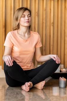 Полный снимок женщина, сидящая со свечой