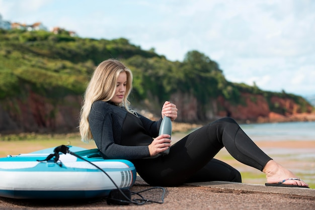 Full shot woman sitting with paddleboard