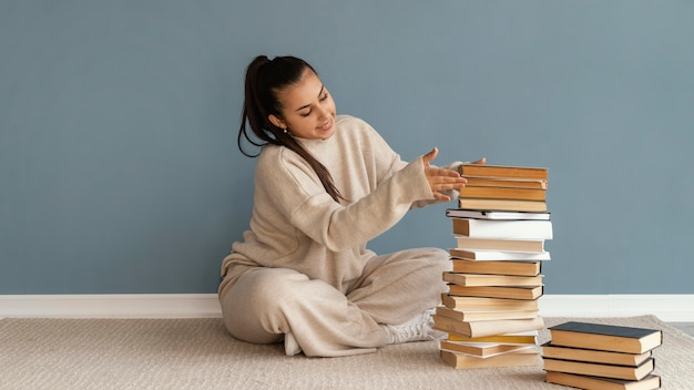 Full shot woman stacking books