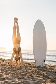 海岸に手で立っているフルショットの女性