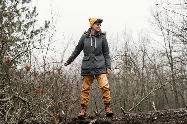 Full shot woman standing on log