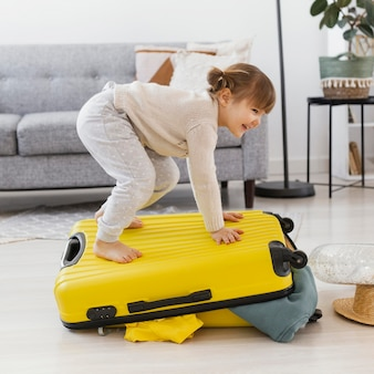 Full shot woman standing on luggage