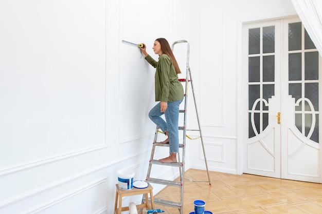 はしごの上に立っているフルショットの女性