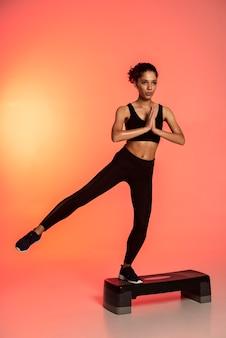 Полный снимок женщины, стоящей на одной ноге
