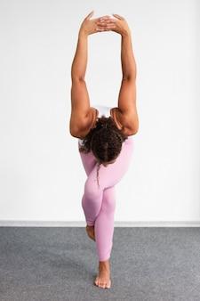 Full shot woman standing on one leg indoors