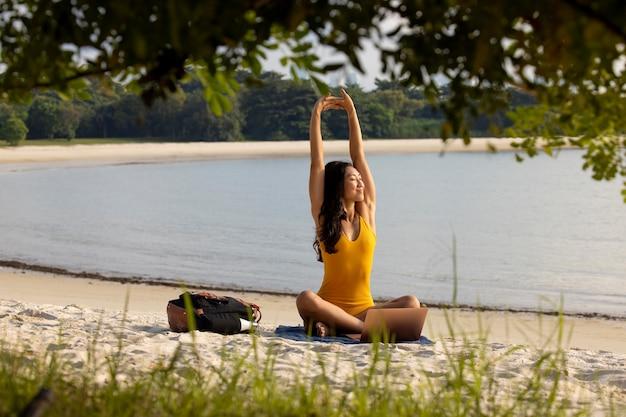 Full shot woman stretching at beach