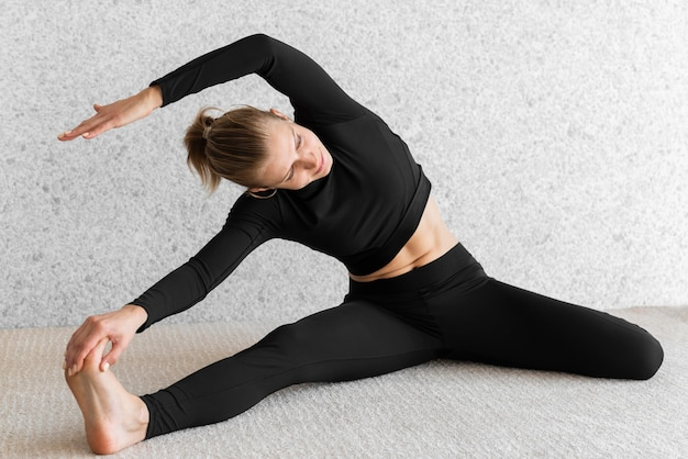 Full shot woman stretching on floor