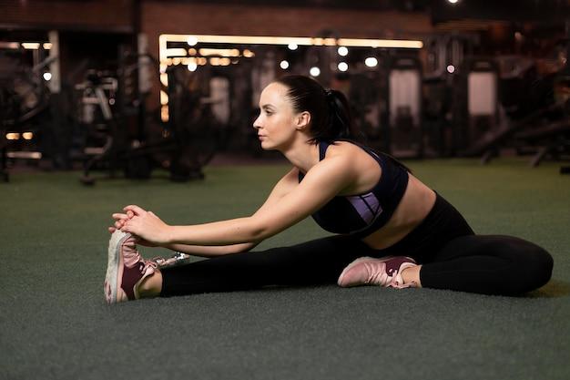 Full shot woman stretching her leg