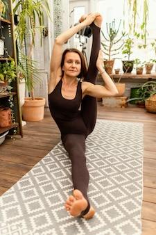 Full shot woman stretching her legs