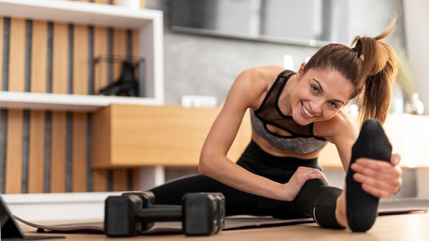 Full shot woman stretching at home
