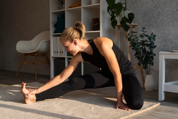 Full shot woman stretching indoors