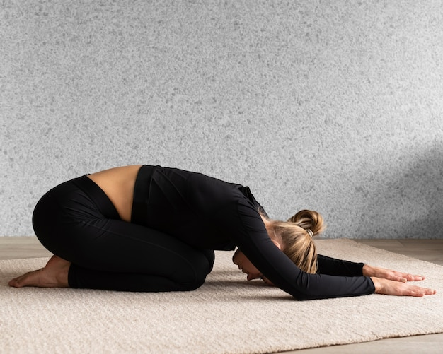 Full shot woman stretching inside