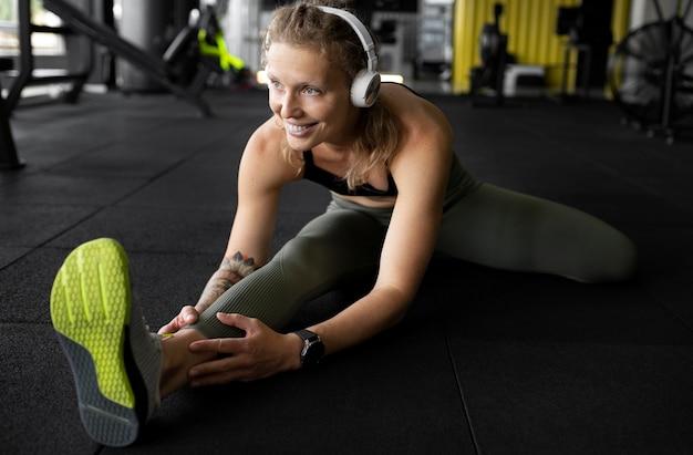 Женщина в полный рост, растягивая ногу в тренажерном зале