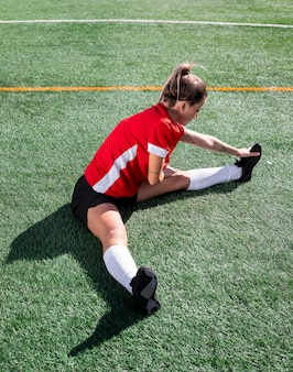Full shot woman stretching leg on field