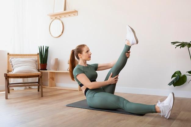 Женщина в полный рост, растягивая ногу