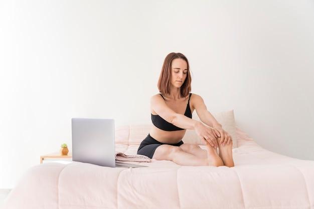 Donna del colpo completo che allunga le gambe a letto