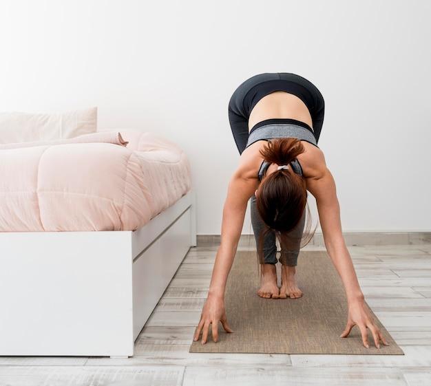 Женщина в полный рост, растягиваясь на коврике дома