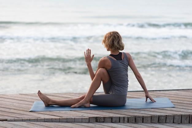 Full shot woman stretching outside near sea