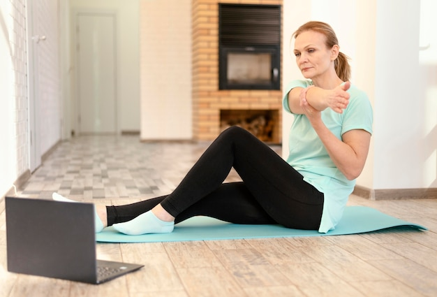 Full shot woman stretching with laptop
