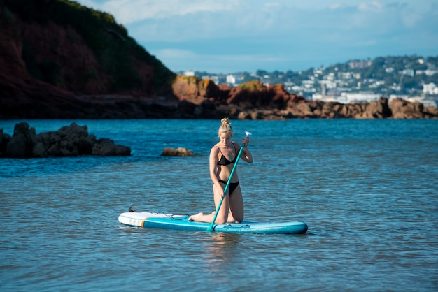 Full shot woman in swimsuit paddleboarding