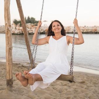 Donna piena del colpo in oscillazione sulla spiaggia